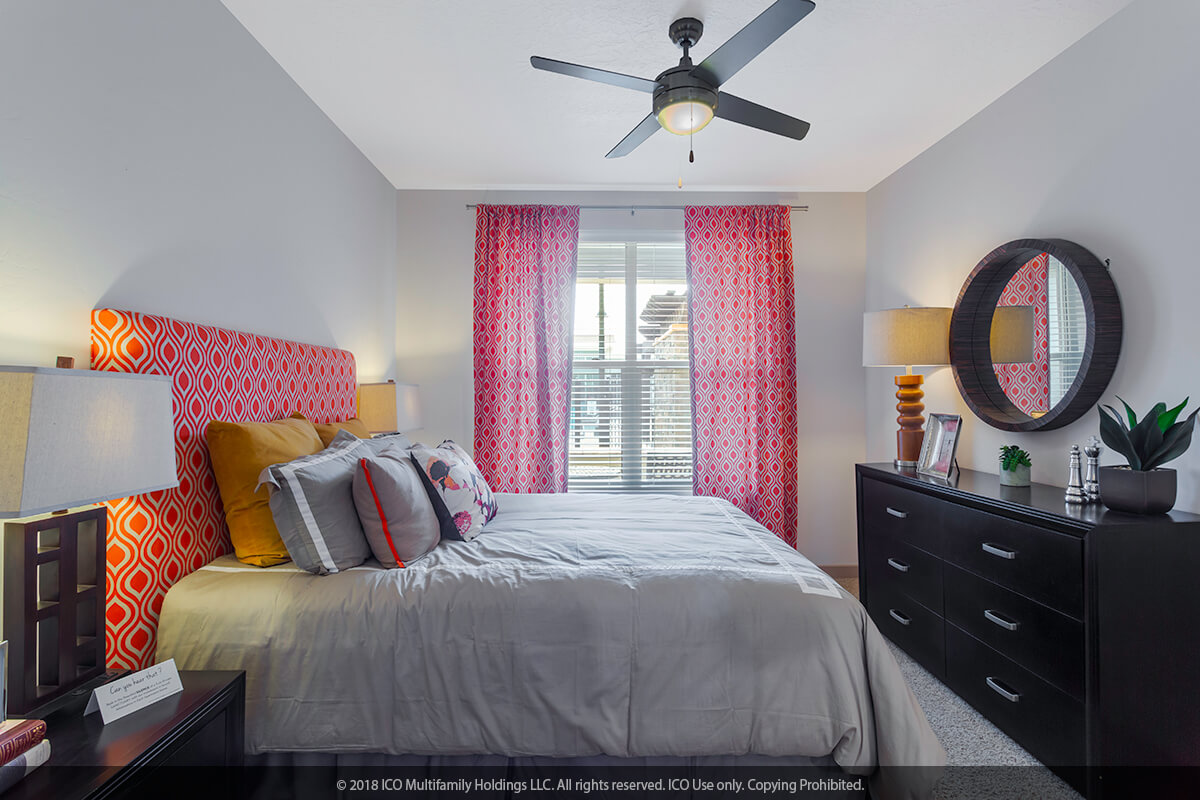Bedroom with ceiling fan and mirrored closet above and windows